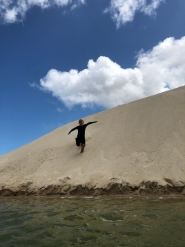 James skidding down the dune into the lagoon