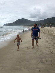 James and Peter walking along the beach to look at the surfing competition going on